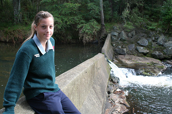 Tessa Berger and the V-notch gauging weir behind the Mahurangi College