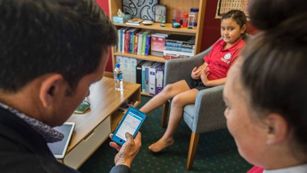 Dr Lance O'Sullivan training school student to use iMoko app
