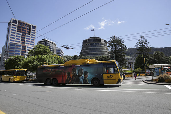 Trolleybus with Executive Wing of the New Zealand Parliament Buildings, the Beehive, in background